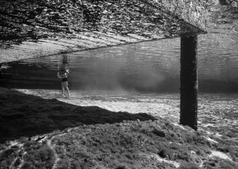 Black and white photograph of a figure submerged underwater