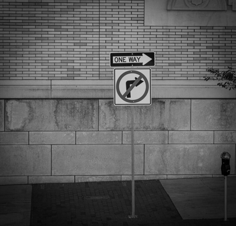 """black and white image, two street signs above one another. One sign states """"one way"""" the other sign is an arrow pointing to the right with a circle negating the arrow. suggesting two divergent messages: """"one way"""" and """"cannot go that way"""""""