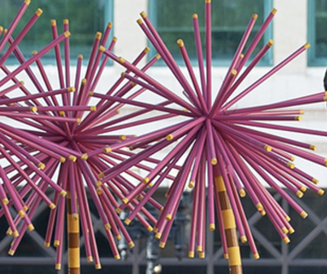 Pink, tubular forms radiate from a central point. Sculptures are outdoors.